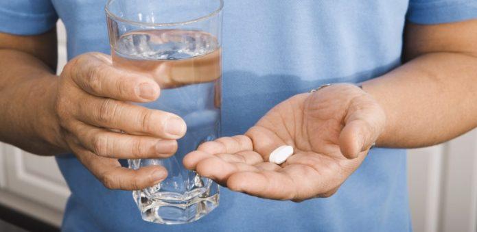 мужчина пьёт таблетку