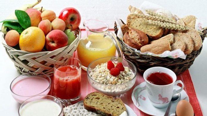 Фрукты, хлеб, овсяные хлопья, йогурт, молоко, сок, чай, яйцо на столе